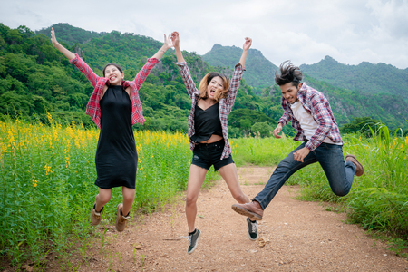 Group of happy young people jumping in the air while traveling in mountain and nature trail. Travel and outdoors lifestyle concept. Stock Photo
