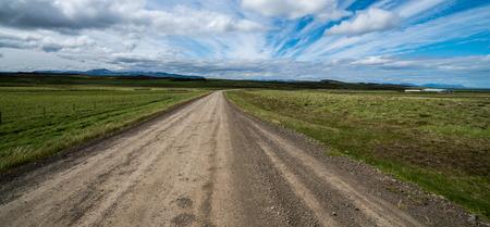 Leerer Schotterweg durch Landschaftslandschaft und Rasenfläche. Natur-Offroad-Reise für ein Allradfahrzeug.