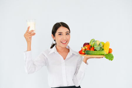 Woman nutritionist presenting diet food of fruit and vegetables for cholesterol control showing awareness and prevention of heart disease.