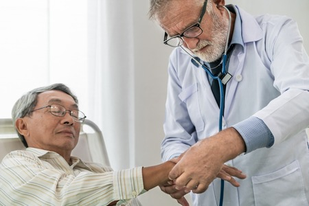 Mature doctor talking and examining health of senior patient in hospital ward.