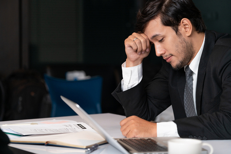 Unhappy young man, businessman feels stress at the office because of economic crisis and awful company loss. Business failure concept. 版權商用圖片