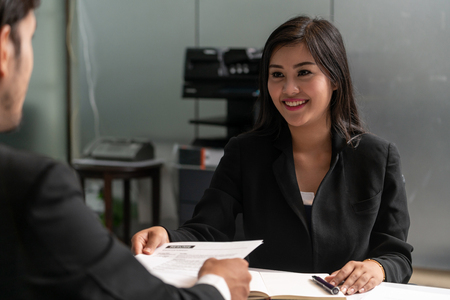 Human resource manager interviewing the male employment candidate in the office room. Happy job interview. Job application, recruitment and Asian labor hiring concept. Stock Photo
