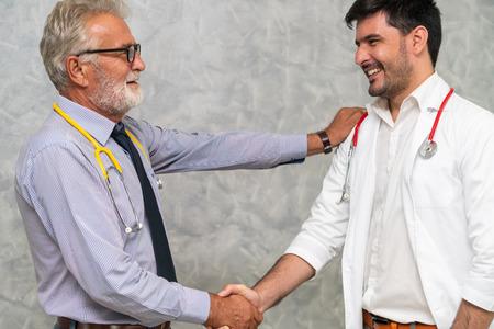 Doctor en apretón de manos del hospital con otro médico. Concepto de servicio de personal médico y trabajo en equipo de personas sanitarias.