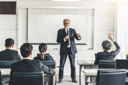 Senior leader speaker speaks to public people audience in training workshop or conference.