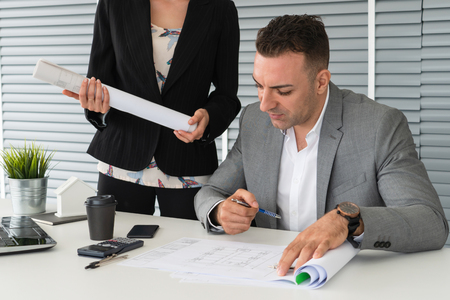 Businessman executive checking work while meeting discussion with businesswoman worker in modern workplace office.