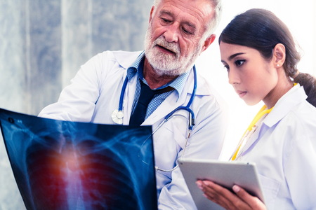 Senior male doctor looking at x ray film of patient chest injury while working with another doctor at the hospital. Medical healthcare staff and doctor service.