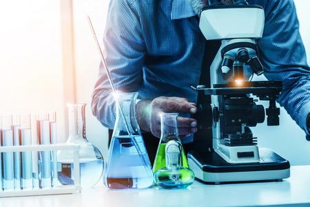 Junge Wissenschaftlerin, die im chemischen Labor arbeitet und Biochemie-Laborprobe untersucht. Wissenschaftstechnologie Medizin Forschungs- und Entwicklungsstudienkonzept.
