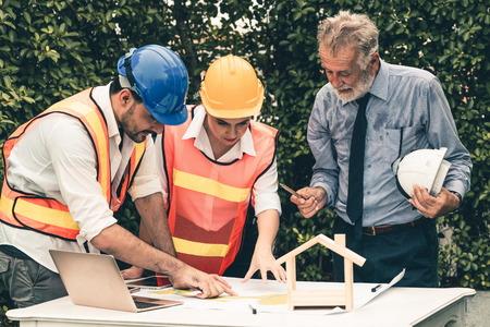 Ingegnere, architetto e uomo d'affari che lavora al progetto di ingegneria in cantiere. Concetto di costruzione di casa. Archivio Fotografico