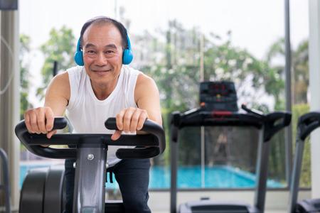 Älterer Mann Übung auf Fahrradmaschine im Fitnesscenter. Reifer gesunder Lebensstil. Standard-Bild