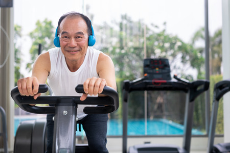 Senior man exercise on cycling machine in fitness center. Mature healthy lifestyle.