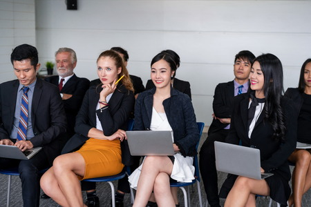 Young Asian and Caucasian audience sitting and listen to speaker in group meeting presentation at the office. Businessmen and businesswomen in training workshop. International multicultural business.