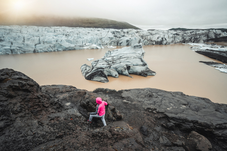 Woman traveler travels at beautiful scenery landscape of Svinafellsjokull Glacier lake, tourism destination in Vatnajokull National Park in Iceland. Cold winter ice landscape.