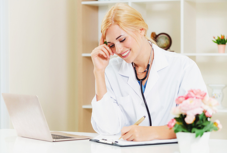Young female doctor working in hospital office. Medical and healthcare concept.