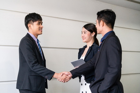 Business people agreement concept. Businessman do handshake with another businessman in the office meeting room. Young Asian secretary lady stands beside them.