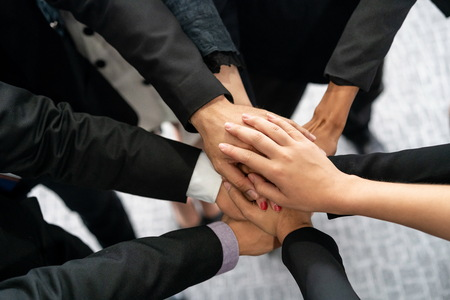 Many happy business people stacking hands together with joy and success. Company employee celebrate after finishing successful work project. Corporate partnership and achievement concept.