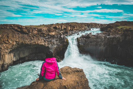 Traveler hiking in Icelandic summer landscape at the Aldeyjarfoss waterfall in north Iceland. The waterfall is situated in the northern part of the Sprengisandur Road within the Highlands of Iceland.