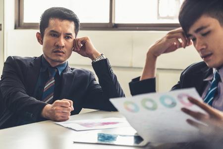 Unglücklicher Geschäftsführer und junger Geschäftsmann im Besprechungsraum im Büro. Sie stehen unter Stress wegen eines schlechten Finanzdokumentberichts. Krisenkonzept des Unternehmens. Standard-Bild