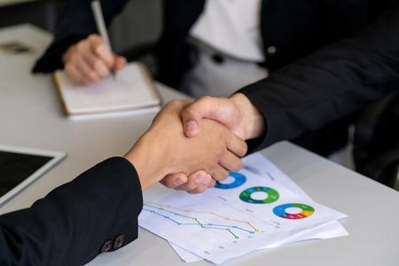 Business mensen overeenkomst concept. Zakenman en Aziatische zakenvrouw doen handdruk op kantoor.