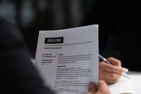 Human resources department manager reads CV resume document of an employee candidate at interview room. Job application, recruit and labor hiring concept.