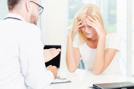 Der männliche Arzt spricht mit einer ernsthaften Patientin im Krankenhausbüro. Gesundheitswesen und medizinischer Service.