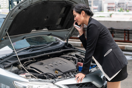 Young businesswoman whose car breakdown uses mobile phone to call for roadside assistance service. Travel and transportation vehicle problem.