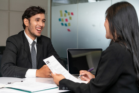 Human resource manager interviewing the male employment candidate in the office room. Happy job interview. Job application, recruitment and Asian labor hiring concept.