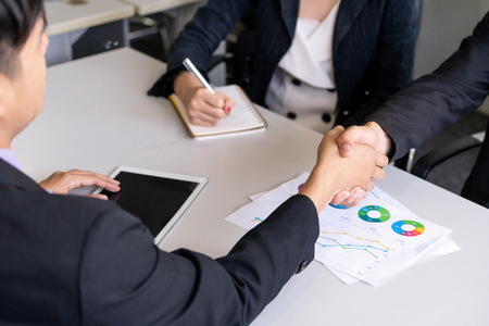 Business people agreement concept. Asian Businessman do handshake with another businessman in the office meeting room. Young Asian secretary lady sits beside him. Standard-Bild