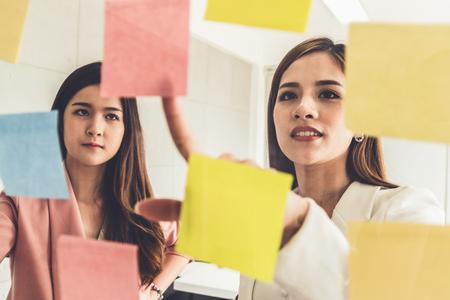 Kreative asiatische Geschäftsfrau in Meeting-Workshop mit vielen positiven Ideen zur Entwicklung ihres Unternehmensgeschäfts. Gruppendiskussion und Brainstorming-Konzept.