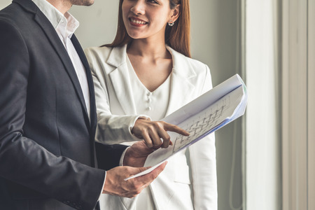 Businessman executive is in meeting discussion with businesswoman or client in modern workplace office. People corporate business team concept.