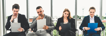 Femmes d'affaires et hommes d'affaires détenant un dossier CV en attendant sur des chaises au bureau pour un entretien d'embauche. Concept d'entreprise et de ressources humaines.