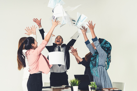 Smiling business people having fun by throwing papers in the air celebrating business success in the modern office. Happy workplace and casual career company concept.