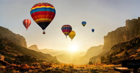 Bellissimo paesaggio naturale panoramico delle montagne di campagna con colorato festival di mongolfiere nel cielo estivo. Fondo di panorama di viaggio di vacanza.
