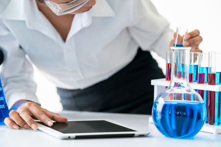 Woman scientist working in laboratory and examining biochemistry sample in test tube. Science technology research and development study concept. Stock Photo