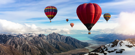 Beautiful panoramic nature landscape of countryside mountains with colorful high hot air balloons festival in summer sky. Vacation travel panorama background. Standard-Bild - 120801049