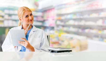 Apotheker die tabletcomputer met behulp van bij de apotheek. Dienst medische zorg en farmaceutisch personeel.