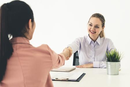 Zwei junge Geschäftsfrauen treffen sich am Bürotisch zur Bewerbung und Geschäftsvereinbarung. Einstellungs- und Personalkonzept. Standard-Bild