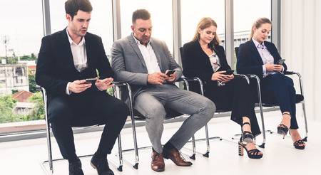 Businesswomen and businessmen using mobile phone while waiting on chairs in office for job interview. Corporate business and human resources concept. 스톡 콘텐츠