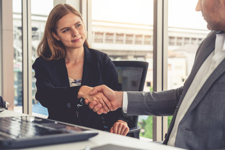 Businessman executive handshake with businesswoman worker in modern workplace office. People corporate business deals concept. Фото со стока