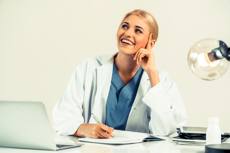 Woman doctor in hospital or healthcare institute working on medical report at office table.