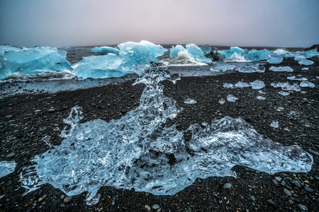 Icebergs on Diamond Beach in Iceland. Frozen ice on black sand beach known as Diamond Beach flows from Jokulsarlon beautiful Glacial Lagoon in Vatnajokull National Park, southeast Iceland, Europe. Stock Photo