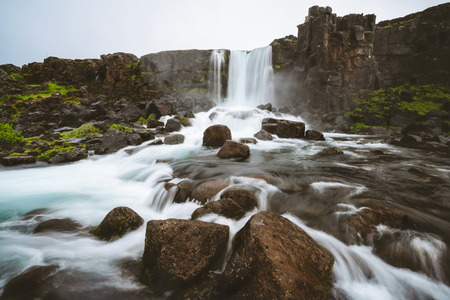 Landscape of Oxararfoss waterfall in Thingvellir National Park, Iceland. Oxararfoss waterfall is the famous waterfall attracting tourist to visit Thingvellir located in route of Iceland Golden Circle. 스톡 콘텐츠