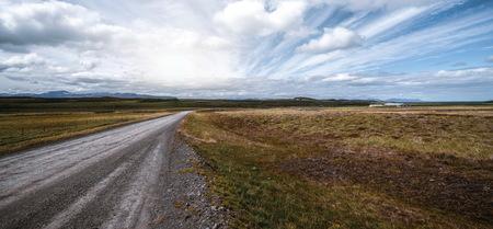 Camino de tierra de grava vacía a través del paisaje y el campo de hierba. Viaje por la naturaleza fuera de la carretera para vehículos con tracción en las cuatro ruedas.