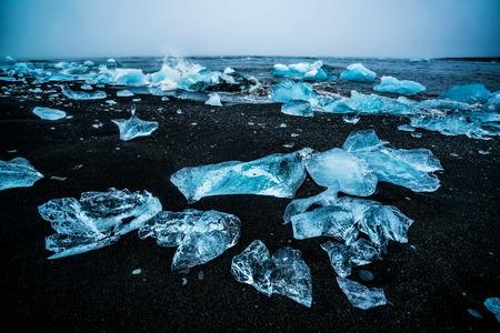 Icebergs on Diamond Beach in Iceland. Frozen ice on black sand beach known as Diamond Beach flows from Jokulsarlon beautiful Glacial Lagoon in Vatnajokull National Park, southeast Iceland, Europe. Stock fotó
