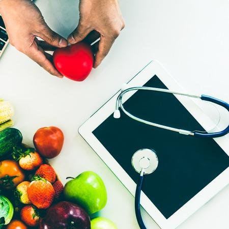Alimentation diététique de fruits et légumes pour le contrôle du cholestérol avec des mains de nutritionniste montrant la sensibilisation et la prévention des maladies cardiaques. Une alimentation saine et un bon concept de nutrition.