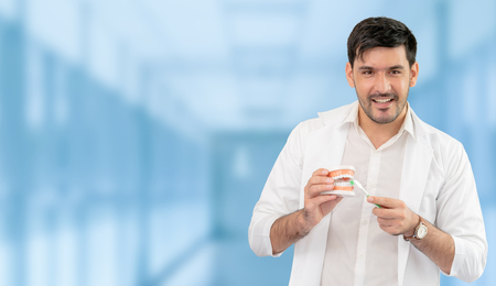 Young male dentist working in dental clinic. Dentistry care and medical service concept. Stockfoto