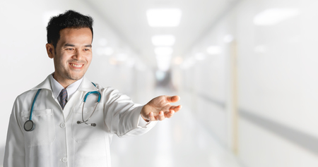 Male doctor at hospital opening hand palm to build copy space for your text and design. Medical healthcare business and doctor service.