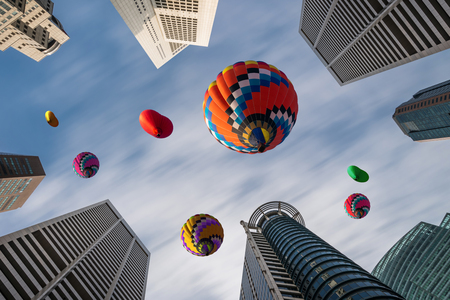 Beautiful panoramic urban cityscape in modern metropolis with colorful high hot air balloons festival in summer sky. Vacation travel panorama city background.