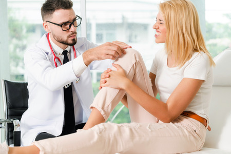 Male doctor is examining female patient in hospital ward. Healthcare and medical service.