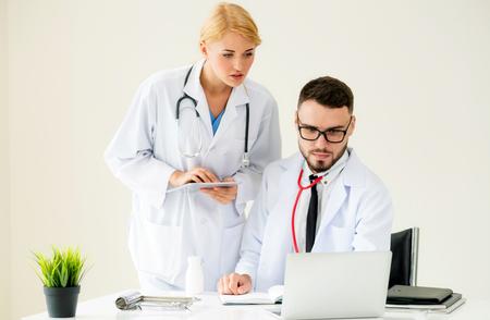 Arzt im Krankenhausbüro, der an einem Laptop auf dem Tisch mit einem anderen Arzt arbeitet, der Diskussion über die Gesundheit des Patienten hat.