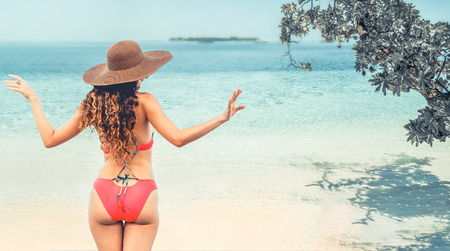 Happy young woman wearing swimsuit at tropical sand beach resort in summer for holiday travel vacation. Stockfoto